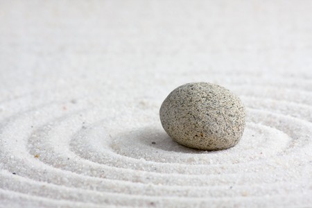 Close up of sand zen garden with stone photo