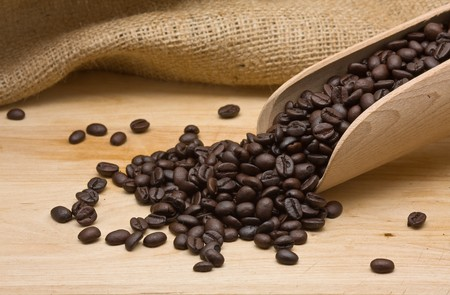 Coffee beans with wooden scoop on wood photo