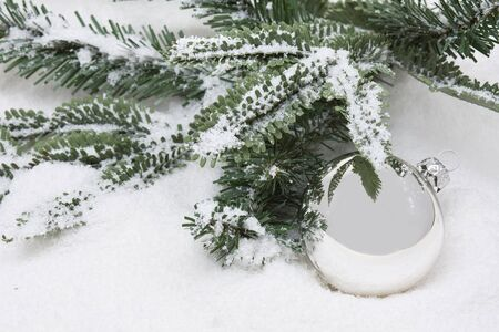 christmas concept: Silver christmas bauble with branch on snow background - winter or christmas concept Stock Photo