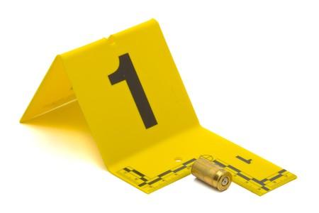 escena del crimen: Marcador de pruebas con carcasa de bala sobre fondo blanco