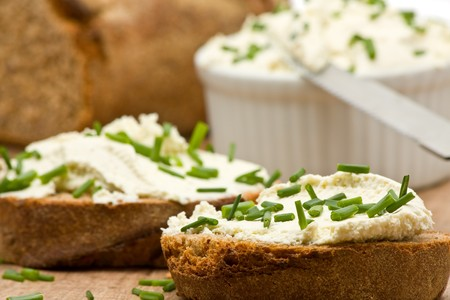 cebollines: Deliciosa crema de queso, el pan en rodajas fresco con cebollines  Foto de archivo