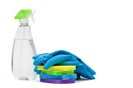 Cleaner with rubber gloves and sponges over white background photo