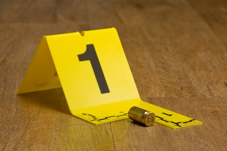 csi: Evidence marker with bullet casing on wooden floor