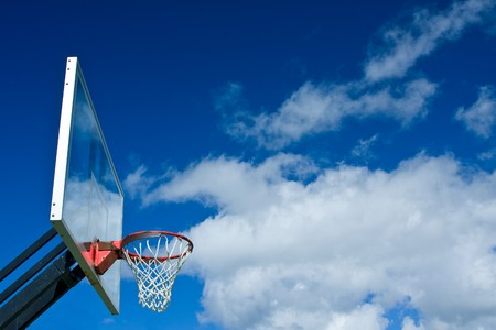 outdoor basketball court: Outdoor basketball hoop with blue sky and clouds