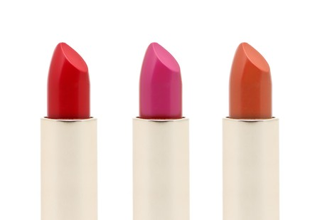 Close up of three lipsticks in different colors isolated on white photo