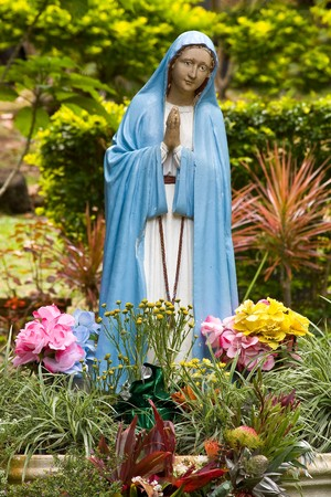 Colorful portuguese Virgin Mary statue in garden photo