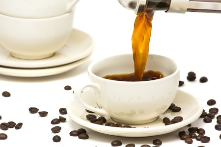 Pouring fresh brewed coffee into ceramic cup photo
