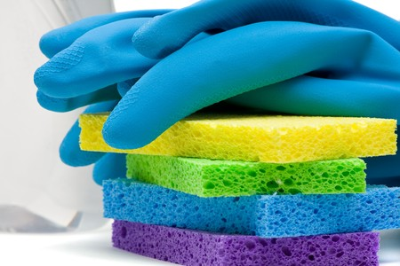Close up of rubber gloves and sponges over white background photo