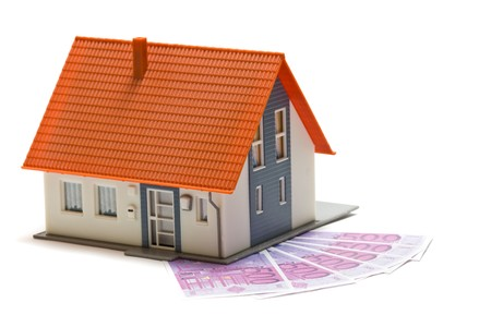 mortgaging: House with money over white background - mortgaging concept Stock Photo