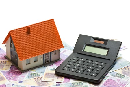 House with money and calculator over white background - mortgaging concept photo