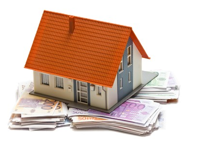 House with money over white background - mortgaging concept photo