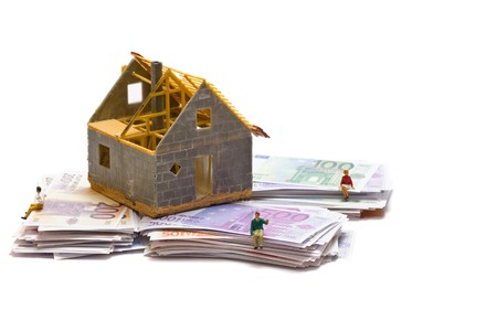 House with money over white background - mortgaging concept Stock Photo