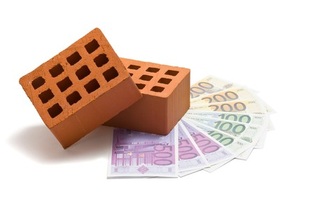 mortgaging: Bricks with money over white background - mortgaging concept