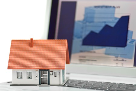 economise: Model house in front of computer with financing plan - mortgaging or home financing concept Stock Photo