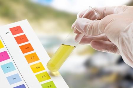 Hand holding Reagenzglas mit pH-Indikator Vergleichen von Farbe zu skalieren