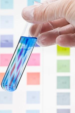 tubo de ensayo: Mano sosteniendo el tubo de ensayo con indicador de pH comparaci�n de color para ajustar la escala