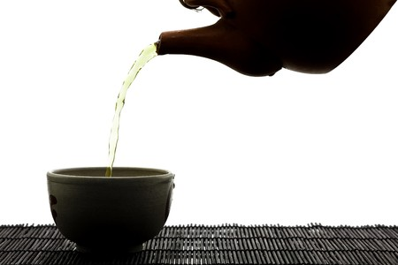 SIlhouette of green tea being poured into ceramic cup photo