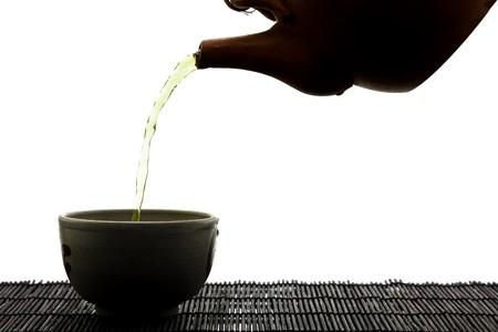 SIlhouette von grünem Tee wird in keramische Tasse gegossen