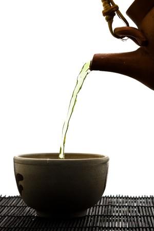 wei�er tee: SIlhouette von gr�nem Tee wird in keramische Tasse gegossen
