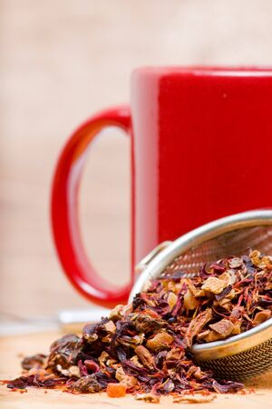 Dried fruit tea in tea strainer with cup of tea photo