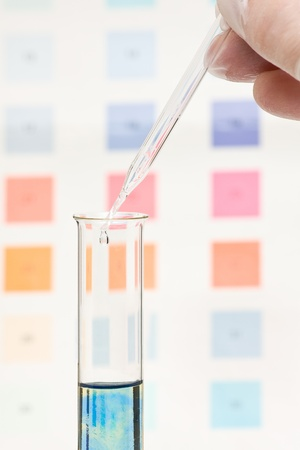 Hand dripping pH indicator into test tube with visible color change in test fluid photo