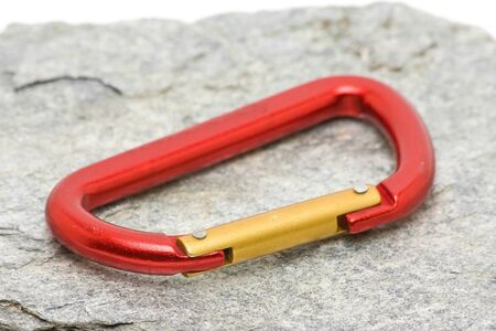 Single red climbing carabiner on grey rock Stock Photo - 8278700