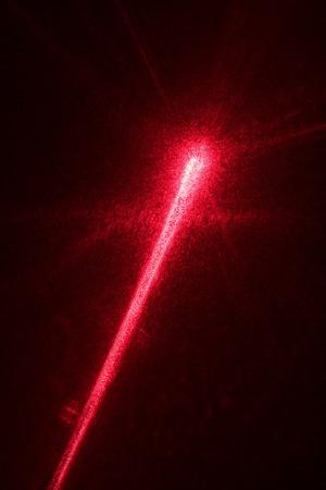 Impacto de rayo láser rojo sobre fondo negro