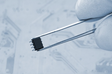 Hand holding microchip with pair of tweezers photo