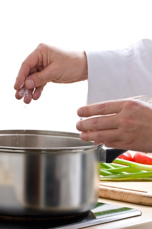 Male chef seasoning meal with fresh sea salt Imagens