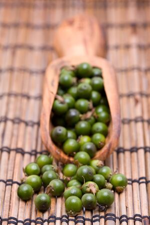 unprocessed: Unprocessed fresh green peppercorns in wooden scoop Stock Photo