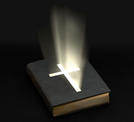 bible and cross: Holy bible with shining cross over black background