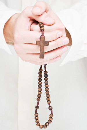 Close up of male hands praying with rosary Stock Photo - 8747268