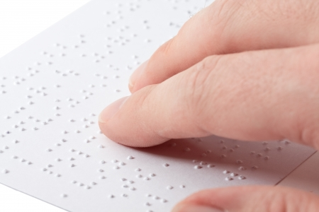 visually: Close up of male hand reading braille text