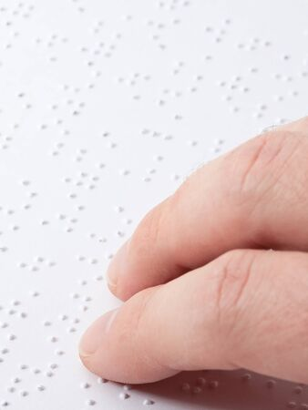 Close up of male hand reading braille text photo