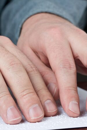 visually: Close up of male hands reading braille text
