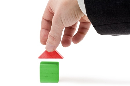 Man holding roof of toy house - real estate concept photo