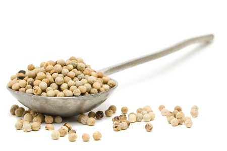 peppercorns: White peppercorns on metal spoon over white background Stock Photo
