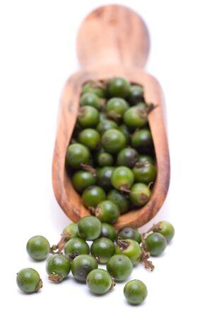 Unprocessed fresh green peppercorns in wooden scoop photo