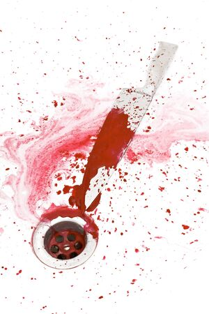 Bloody knife in the shower with blood flowing into the drain photo