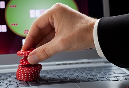gambling game: Player placing chips on a laptop which shows an online casino - online gambling concept Stock Photo