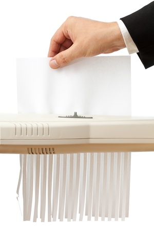 Business man puts single piece of paper in shredder; empty paper with copyspace photo