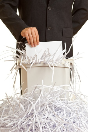 Business man shredding confidential documents at overflowing shredder photo