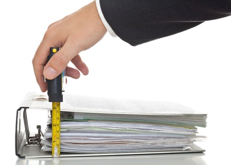 ring binder: Businessman checks level of performed work - performance or financial analysis concept; focus on the ruler