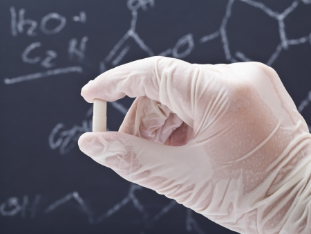 Medical researcher examining pill in front of blackboard with formula photo