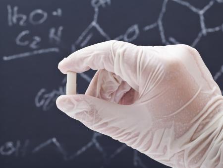 Medizinische Forscher untersuchen Pille vor der Tafel mit Formel Lizenzfreie Bilder