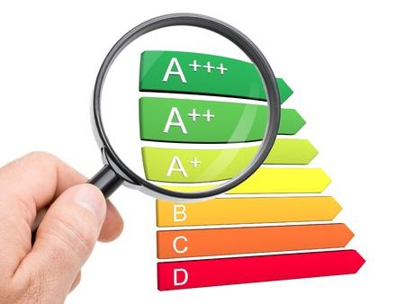 eficacia: Mano con lupa mirando el nuevo A +, A ++ y A +++ clases de la clasificaci�n de eficiencia energ�tica europea Foto de archivo