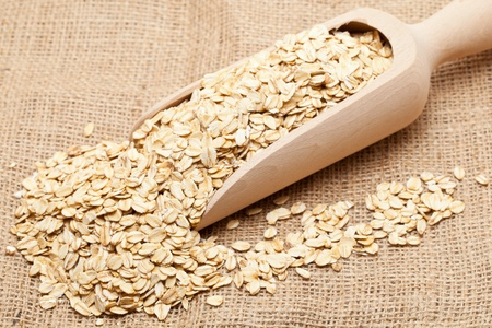 Oat flakes in wooden scoop on burlap background photo