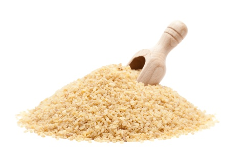 Raw dried couscous with wooden scoop isolated on white background Stock Photo - 10529266