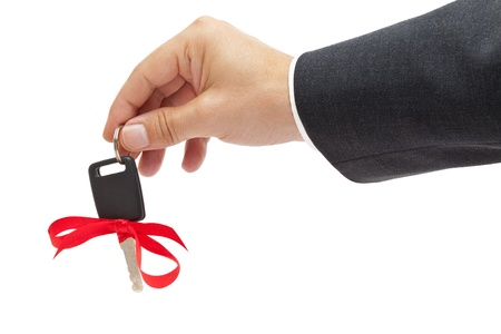 buying a car: Handing over car key with red bow as a present
