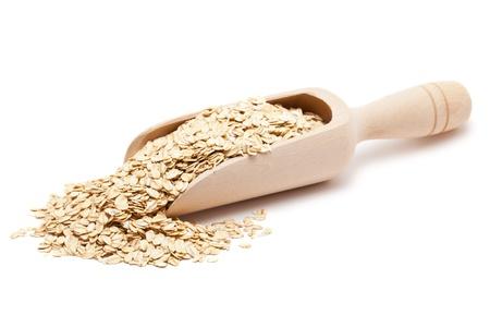 avena: Copos de avena en la cuchara de madera aisladas sobre fondo blanco